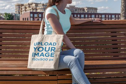 Tote Bag Mockup of a Young Woman Sitting on a Park Bench 197-el
