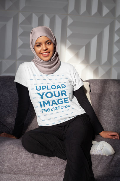 Shirt Mockup of a Smiling Woman With a Hijab Sitting in the Living Room 28402