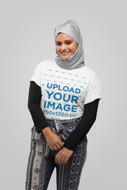 T-Shirt Mockup of a Young Woman Wearing a Hijab Against a Solid Color Backdrop 28387