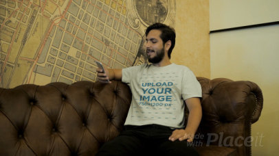 T-Shirt Video of a Man Sitting on a Vintage Couch Checking His Phone 28924