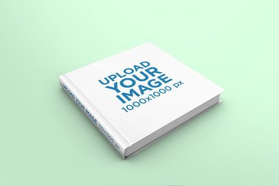 Mockup Featuring a Hardcover Square Book Lying on a Solid Color Surface 296-el
