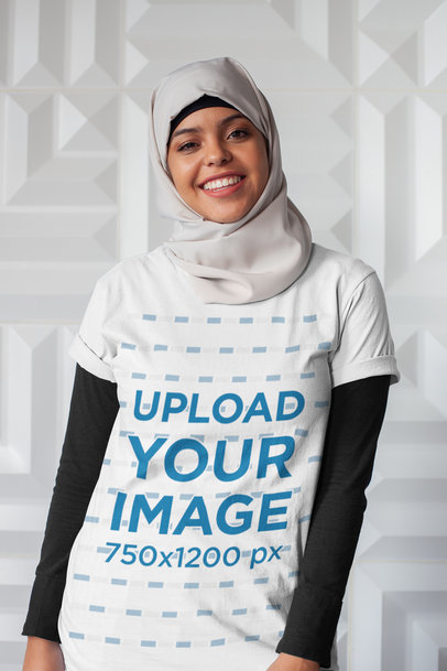T-Shirt Mockup of a Woman with a Hijab Against a White Textured Wall 28398