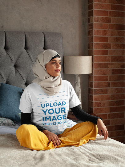 T-Shirt Mockup of a Woman in a Hijab Sitting Thoughtful on Her Bed 28396