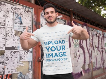 T-Shirt Mockup of a Fitness Man Posing Against a Wall with Posters 28526