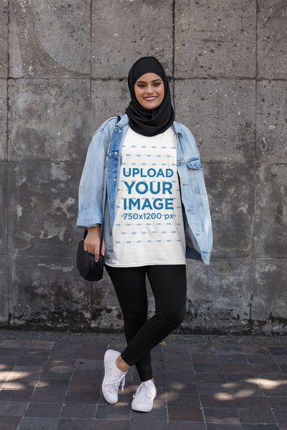 T-Shirt Mockup Featuring a Woman with a Hijab Against a Dark Stone Wall 28388