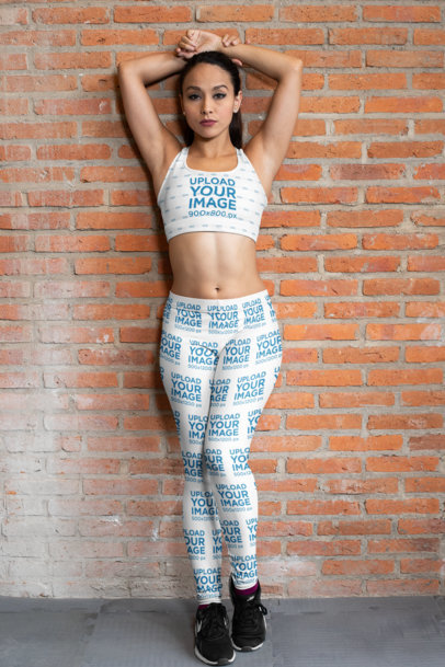 Mockup of a Woman Against a Brick Wall Wearing a Sports Bra and Leggings 28684