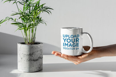 Mockup Featuring a Hand Holding an 11 oz Coffee Mug in a Minimal Setting 402-el