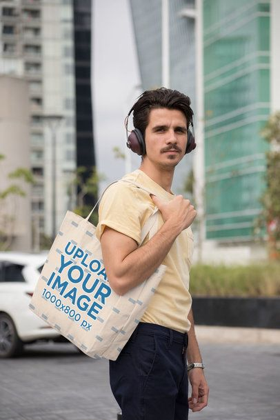 Tote Bag Mockup of a Man with Headphones Walking on the Street 28837