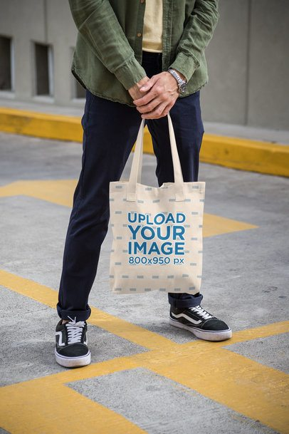 Mockup of a Man Holding a Tote Bag on a Painted Street 28841