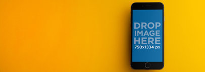 iPhone Mockup in Front of a Yellow Background a9803