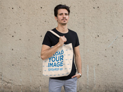 Mockup of a Man Holding a Tote Bag with a Concrete Wall in the Background 28855