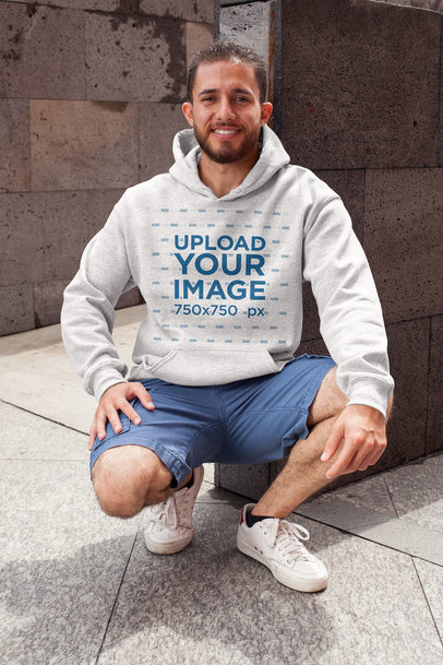 Heathered Hoodie Pullover Mockup Featuring a Smiling Man in a Crouching Position 28629