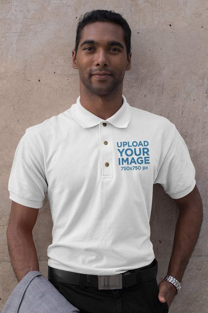 Mockup of a Man Wearing an Embroidered Polo Shirt Against a Concrete Wall 28907