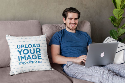 Square Pillow Mockup Featuring a Joyful Young Man Sitting on a Couch 29014