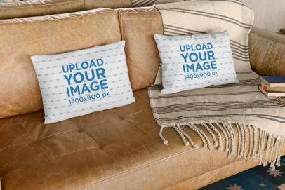 Mockup of Two Pillows on a Leather Sofa with Books on the Side 29005