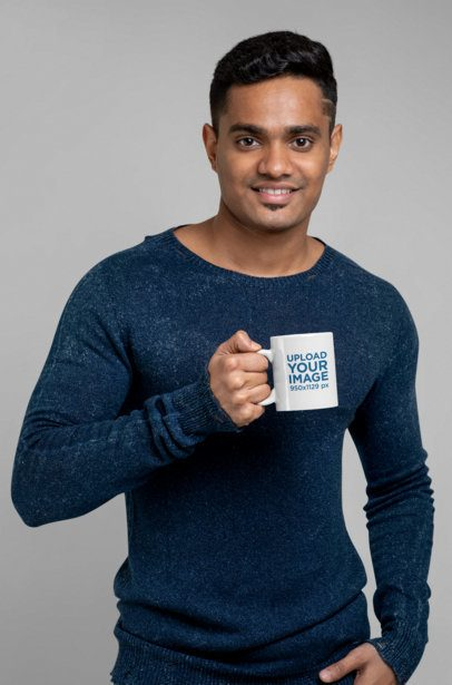 Mockup of a Fit Man Holding an 11 oz Coffee Mug at a Studio 28963