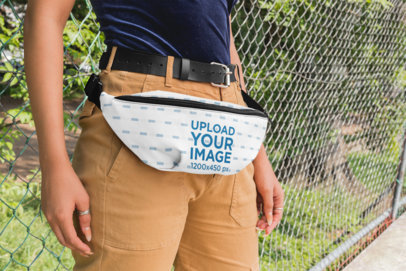 Mockup of a Woman With a Fanny Pack Leaning Against a Chain-link Fence 29141