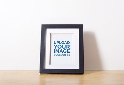 Mockup of a Photo Frame Leaning on a Plain Wall 590-el
