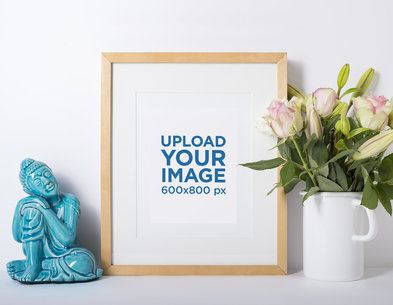 Mockup of a Photo Frame Standing Against a White Wall and Next to Some Flowers 593-el