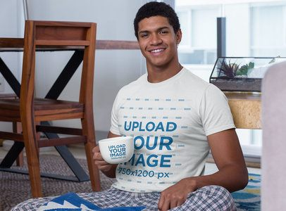 T-Shirt Mockup Featuring a Young Man Holding a 24 oz Mug in the Living Room 29255