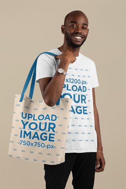 T-Shirt Mockup of a Man Carrying a Customizable Strap Tote Bag Against a Flat Background 29433