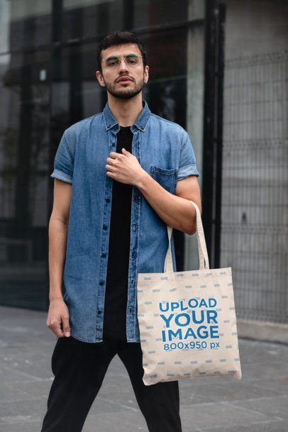Mockup of a Trendy Man Posing with a Tote Bag on the Street 29425