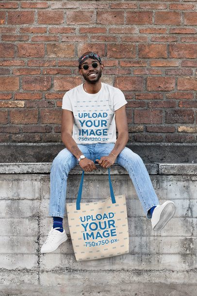 T-Shirt Mockup of a Man with a Tote Bag in Front of an Old Brick Wall 29437