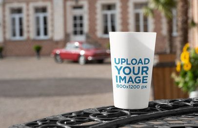 Mockup of a Reusable Cup Placed over a Table 29726