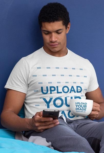 T-Shirt Mockup of a Man Holding a 24 oz Mug While Checking His Phone 29256