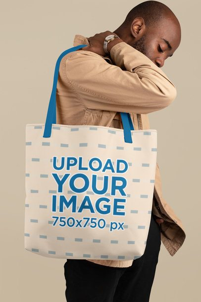 Mockup of a Young Man Carrying a Tote Bag with Customizable Strap at a Studio 29442
