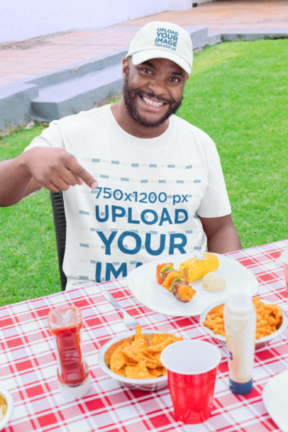 T-Shirt Mockup of a Man with a Dad Hat Pointing at a Table with Food 29713