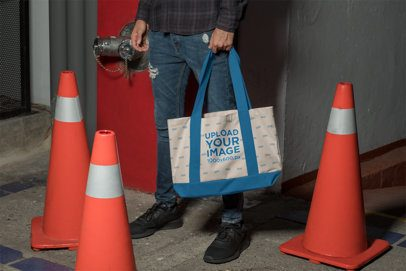 Mockup of a Man Holding a Sublimated Weekend Tote Bag by Traffic Cones 29801
