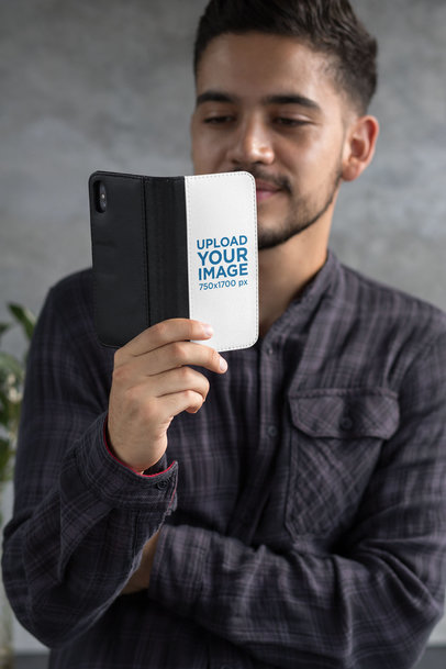 Wallet Case Mockup of a Man Looking at His iPhone X 29819