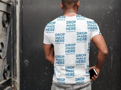 Back of a Black Man Wearing a T-Shirt Mockup while Facing a Wall a9359b