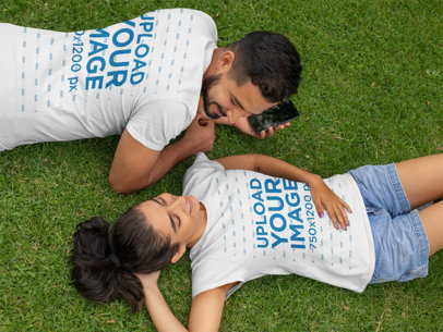 Front and Back T-Shirt Mockup of a Couple Lying on the Grass 29785