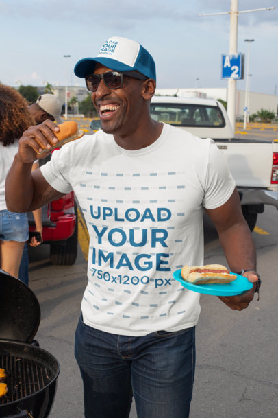 T-Shirt Mockup of a Man with a Trucker Hat Eating at a Tailgate Party 29893