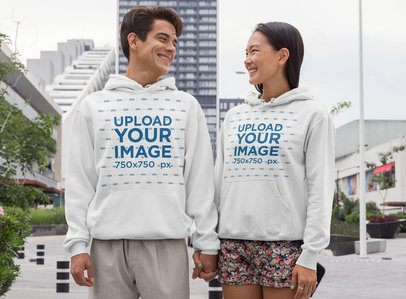 Mockup of a Couple Wearing Hoodies in the City 29773