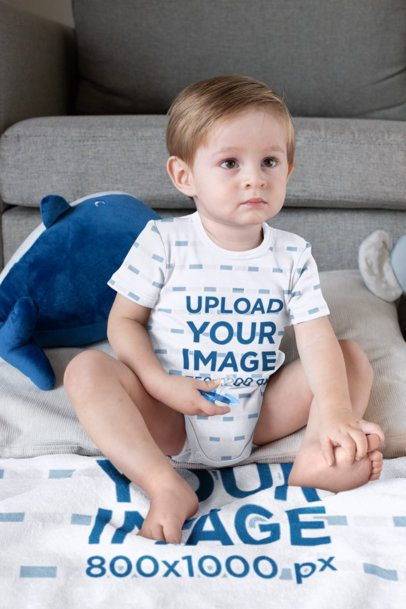 Onesie Mockup of a Boy Sitting on a Sublimated Blanket 30015