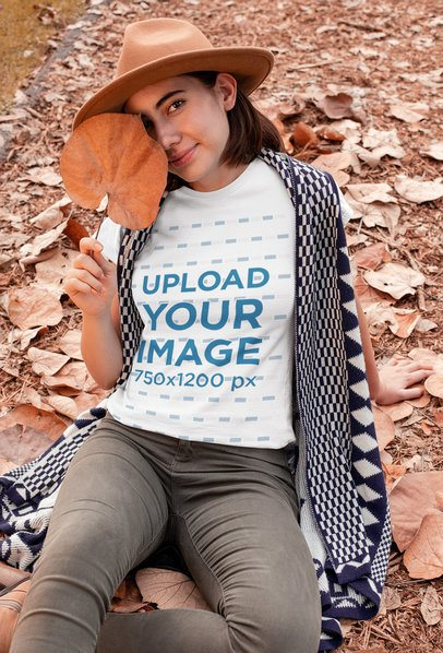 T-Shirt Mockup of a Woman Sitting on a Field with Fall Leaves 30109