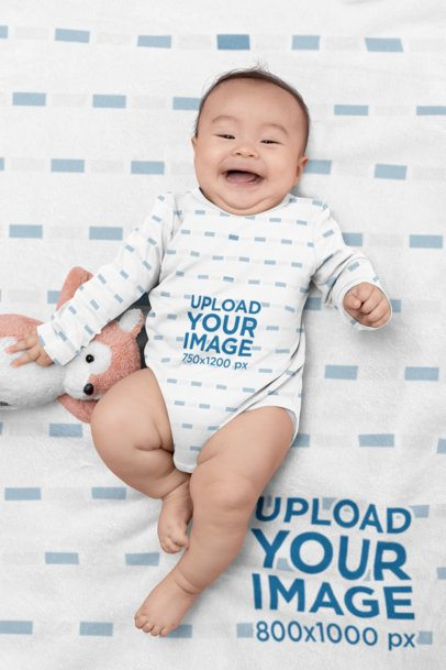 Onesie Mockup of a Cheerful Baby Lying on a Customizable Blanket 30050