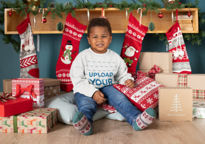 Mockup of a Boy With a Crewneck Sweatshirt Surrounded by Christmas Presents 30361