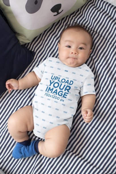 Mockup of a Baby Wearing a Onesie While Lying on a Bed 30013