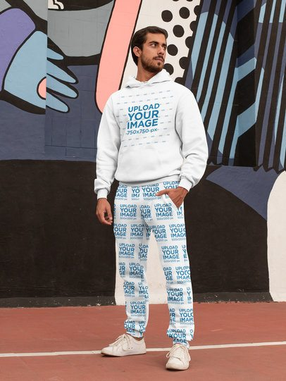 Hoodie Mockup of a Bearded Man Wearing Sweatpants Against a Graffiti Wall 29850