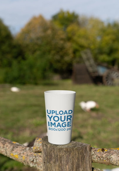 Mockup of a Reusable Cup Placed on a Wooden Fence 30565