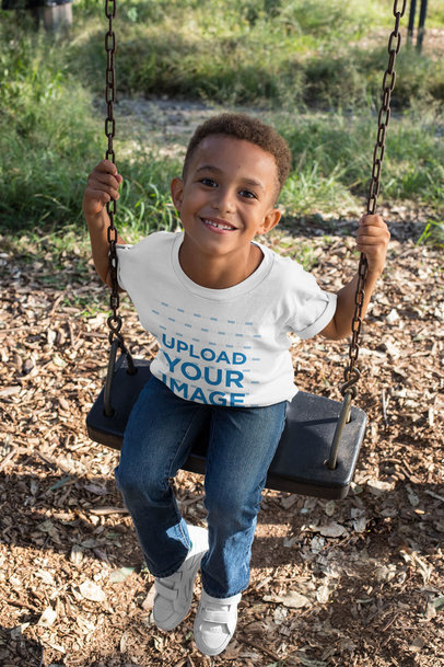 T-Shirt Mockup of a Smiling Boy Playing on a Swing