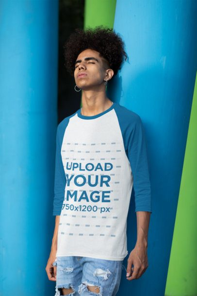 Three-Quarter Sleeves Raglan Tee Mockup Featuring a Young Man Leaning Against a Colorful Column 30221