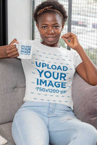 Mockup of a Woman with a T-Shirt Holding an 11 oz Mug While Sitting on a Sofa 30341