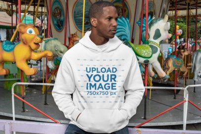 Mockup of a Man Wearing a Pullover Hoodie at a Carousel 30456