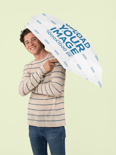 Mockup of a Smiling Man Holding an Umbrella at a Studio 30715