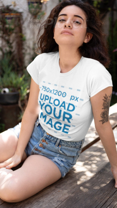 T-Shirt Video of a Young Tattooed Woman Sitting on a Wooden Garden Table 22438